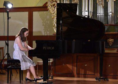 II. absolventský koncert, Refektář Profesního domu MFF, 14.5.2019. Děvče hrající na klavír.