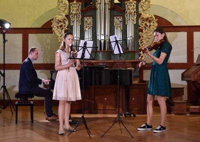 II. absolventský koncert, Refektář Profesního domu MFF, 14.5.2019. Komorní trio - dvě děvčata hrající na zobcovou flétnu a housle a učitel hrající na klavír.