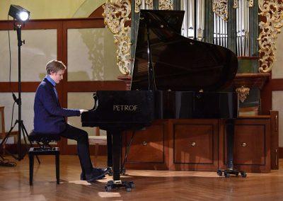 II. absolventský koncert, Refektář Profesního domu MFF, 14.5.2019. Chlapec hrající na klavír.