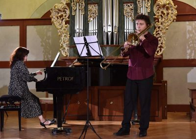 II. absolventský koncert, Refektář Profesního domu MFF, 14.5.2019. Chlapec hrající na pozoun a učitelka hrající na klavír.