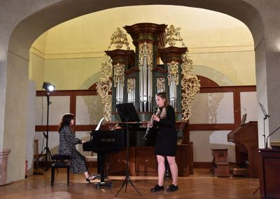 II. absolventský koncert, Refektář Profesního domu MFF, 14.5.2019. Děvče hrající na klarinet a učitelka hrající na klavír.