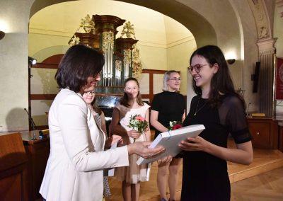 II. absolventský koncert, Refektář Profesního domu MFF, 14.5.2019. Paní ředitelka předává žákyni blahopřání k absolvování studia na ZUŠ.