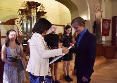 II. absolventský koncert, Refektář Profesního domu MFF, 14.5.2019. Paní ředitelka předává žákovi blahopřání k absolvování studia na ZUŠ.