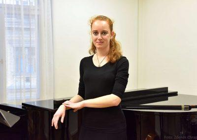 Absolventka hudebního oboru 2018/2019 stojící u klavíru.