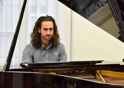 Absolvent hudebního oboru 2018/2019 sedící za klavírem.