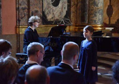 Adventní koncert ZUŠ 7.12.2019 - Klementinum. Pohled na paní klavíristku A. Barthovou a zpívající děvče.
