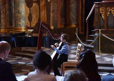 Adventní koncert ZUŠ 7.12.2019 - Klementinum. Pohled na kluka hrajícího na harfu.
