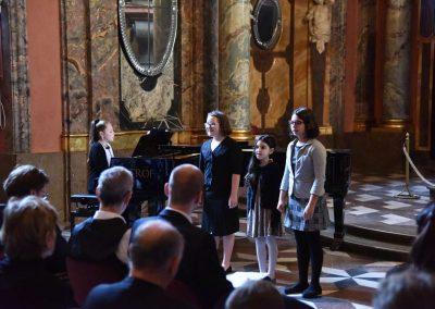 Adventní koncert ZUŠ 7.12.2019 - Klementinum. Pohled na děvče hrající na klavír a další tři zpívající děvčata.