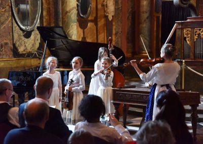 Adventní koncert ZUŠ 7.12.2019 - Klementinum. Pohled na pět zpívajících a hrajících děvčat z lidového souboru.