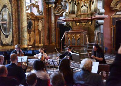 Adventní koncert ZUŠ 7.12.2019 - Klementinum. Pohled na instrumentální soubor, děvče hrající na cimbál, paní učitelka D. Pražáková hrající na violoncello a dva chlapci hrající na violoncello.