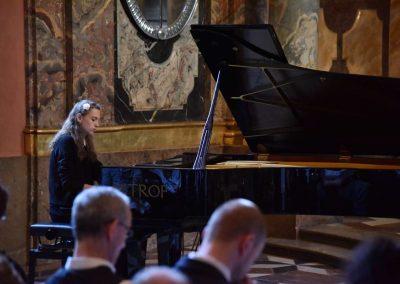 Adventní koncert ZUŠ 7.12.2019 - Klementinum. Pohled na publikum a hrající děvče na klavír.