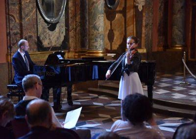 Adventní koncert ZUŠ 7.12.2019 - Klementinum. Pohled na pana klavíristu V. Kopáčika a děvče hrající na housle.