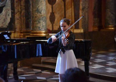 Adventní koncert ZUŠ 7.12.2019 - Klementinum. Pohled na pana děvče hrající na housle.