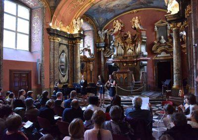 Adventní koncert ZUŠ 7.12.2019 - Klementinum. Pohled na zpívající děvče, děvče hrající na klavír a dvě děvčata hrající na flétnu.