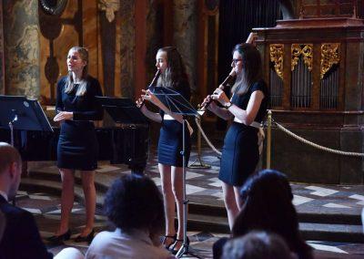 Adventní koncert ZUŠ 7.12.2019 - Klementinum. Pohled na zpívající děvče a dvě děvčata hrající na flétnu.
