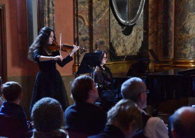 Adventní koncert ZUŠ 7.12.2019 - Klementinum. Pohled na publikum, děvče hrající na housle a paní klavíristku M. Pecikiewiczovou.