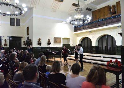 Adventní koncert přípravnýho pěveckýho sborů Pueri gaudentes 15.12.2019. Pohled na hrající flétnové trio - paní učitelka, děvče a kluk.