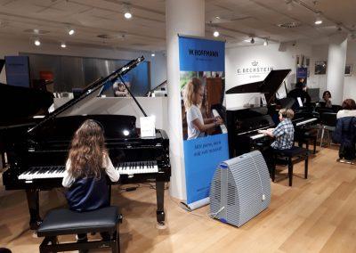 Klavírní koncert D. Rolincové v C. Bechstein Pianocentru 23.01.2020. Žák hrajíci na klavír - děvče. Po pravé straně žák hrající na jiný klavír - chlapec.