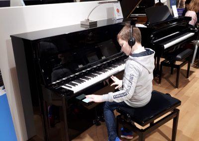Klavírní koncert D. Rolincové v C. Bechstein Pianocentru 23.01.2020. Žák hrající na pianino - chlapec.