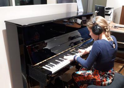 Klavírní koncert D. Rolincové v C. Bechstein Pianocentru 23.01.2020. Žák hrající na pianino - děvče..