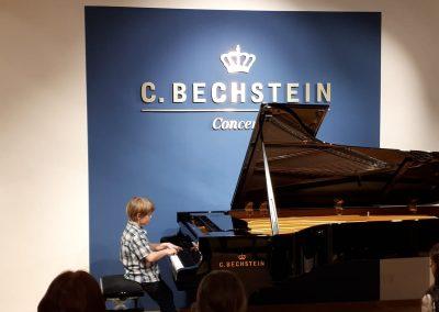 Klavírní koncert D. Rolincové v C. Bechstein Pianocentru 23.01.2020. Žák hrající na klavír - chlapec.