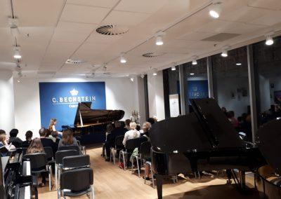 Klavírní koncert D. Rolincové v C. Bechstein Pianocentru 23.01.2020. Žák hrající na klavír - děvče, v popředí diváci..