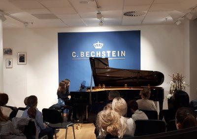 Klavírní koncert D. Rolincové v C. Bechstein Pianocentru 23.01.2020. Žáci hrající na klavír - dvě děvčata, komorní hra.