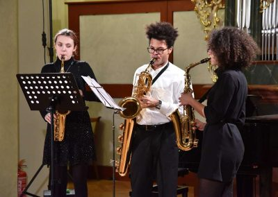 Refektář profesního domu MFF UK, dechový koncert 6.2.2020. Žáci hrající na saxofony, trio - dva chlapci a jedno děvče.