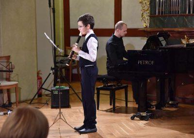 Refektář profesního domu MFF UK, dechový koncert 6.2.2020. Žák hrajíci na altovou zbocovu flétnu - chlapec, v pozadí učitel hrající na klavír.