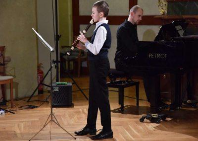 Refektář profesního domu MFF UK, dechový koncert 6.2.2020. Žák hrajíci na zbocovu flétnu - chlapec, v pozadí učitel hrající na klavír.