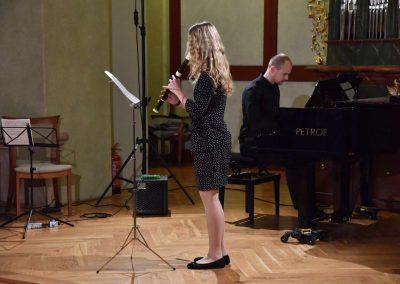 Refektář profesního domu MFF UK, dechový koncert 6.2.2020. Žák hrajíci na zbocovu flétnu - děvče, v pozadí učitel hrající na klavír.