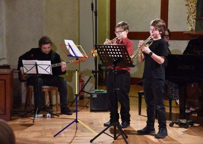 Refektář profesního domu MFF UK, dechový koncert 6.2.2020. Žáci hrajíci na trubky, duo - dva chlapci, v pozadí učitel hrající na basovou kytaru a učitelka hrajíci na kalvír.