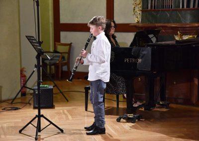 Refektář profesního domu MFF UK, dechový koncert 6.2.2020. Žák hrajíci na klarinet - chlapec, v pozadí učitelka hrající na klavír.