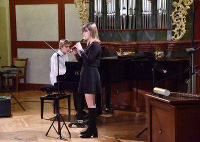 Refektář profesního domu MFF UK, dechový koncert 6.2.2020. Žák hrajíci na zbocovu flétnu - děvče, v pozadí učitelka hrající na klavír.