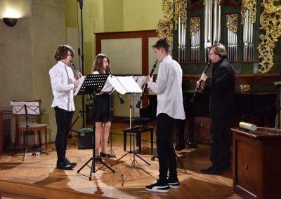 Refektář profesního domu MFF UK, dechový koncert 6.2.2020. Žáci a učitel hrajíci na klarinety, kvarteto - dva chlapci, jedno děvče a jeden učitel.