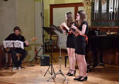 Refektář profesního domu MFF UK, dechový koncert 6.2.2020. Žáci hrajíci na zobcové flétny, duo - dvě děvčata, v pozadí učitel hrající na basovou kytaru a učitelka hrajíci na kalvír.
