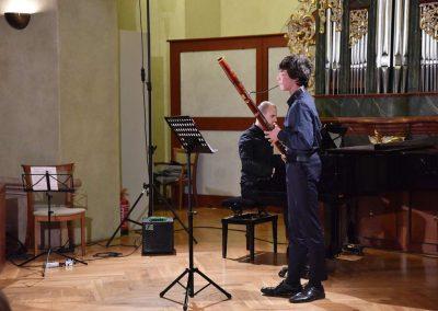 Refektář profesního domu MFF UK, dechový koncert 6.2.2020. Žák hrajíci na fagot - chlapec, v pozadí učitel hrající na klavír.