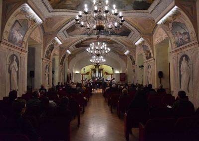 Refektář profesního domu MFF UK, dechový koncert 6.2.2020. Žáci hrajíci na flétny, flétnový soubor, v popředí sedící diváci. Pohled na jeviště z pozice diváků.