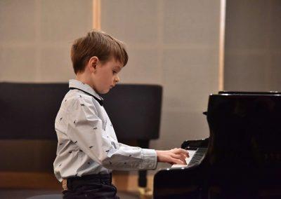 Galerie HAMU, klavírní koncert 11.2.2020. Žák hrající na klavír - chlapec