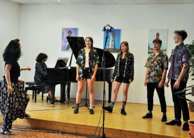 Natáčení absolventů, 23.6.2020, komorní sál ZUŠ Šimáčkova. Dvě zpívající děvčata, dva zpívající chlapci, paní učitelka hrající na klavír a paní sbormistryně.