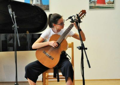 Natáčení absolventů, 23.6.2020, komorní sál ZUŠ Šimáčkova. Děvče hrající na kytaru.