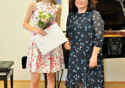 Natáčení absolventů, 23.6.2020, komorní sál ZUŠ Šimáčkova. Děvče s kyticí, vysvědčením a velde ní sotjí paní učitelka.