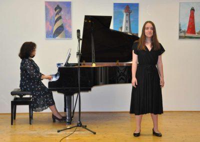 Natáčení absolventů, 23.6.2020, komorní sál ZUŠ Šimáčkova. Zpívající děvče a paní učitelka hrající na klavír.