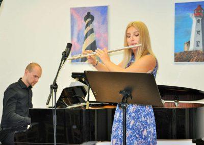 Natáčení absolventů, 23.6.2020, komorní sál ZUŠ Šimáčkova. Děvče hrající na příčnou flétnu a pan učitel hrající na klavír.