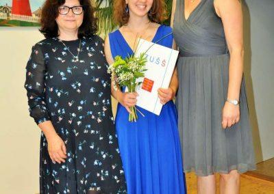 Natáčení absolventů, 23.6.2020, komorní sál ZUŠ Šimáčkova. Vlevo stojí paní učitelka, veprostřed děvče s kyticí a vysvědčením, vpravo stojí paní učitelka.