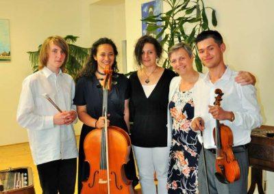 Natáčení absolventů, 23.6.2020, komorní sál ZUŠ Šimáčkova. Společná fotografie, vlevo chlapec, vedle něj děvče s violoncellem, vedlě ní paní učitelka, vedle ní další paní učitelka a chlapec s houslemi.
