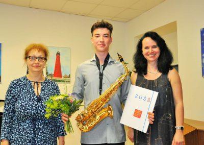 Natáčení absolventů, 24.6.2020, komorní sál ZUŠ Šimáčkova. Vlevo stojící učitelka,veprostřed chalpec se saxofonem, vpravo stojící učitelka.