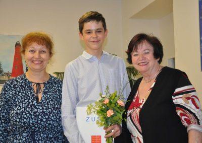 Natáčení absolventů, 24.6.2020, komorní sál ZUŠ Šimáčkova. Vlevo stojí paní učitelka, veprostřed chlapec s kyticí a vysvědčením, vpravo stojí paní učitelka.
