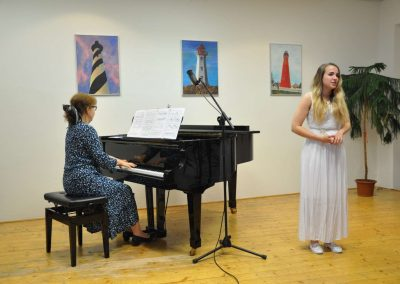 Natáčení absolventů, 24.6.2020, komorní sál ZUŠ Šimáčkova. Zpívající děvče a apní učitelka hrající na klavír.