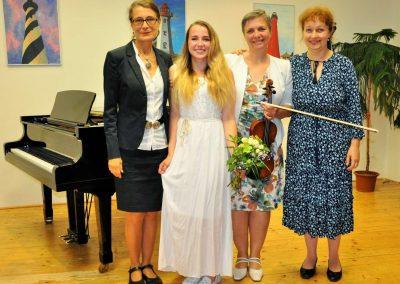 Natáčení absolventů, 24.6.2020, komorní sál ZUŠ Šimáčkova. Vlevo paní učitelka, vedle ní stojí děvče, vedle ní paní učitelka a vedle ní paní učitelka.